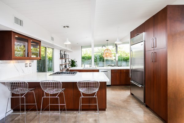 The light-filled, modern kitchen has been updated with a marble-topped peninsula with breakfast-bar seating and plenty of storage. It also features Viking appliances including a built-in, stainless steel SubZero refrigerator.