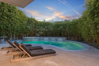 At a lavish home in Los Angeles, the kidney-shaped swimming pool is shaded and private. There is also an outdoor shower area.