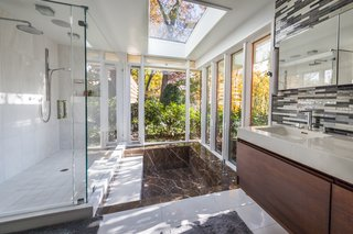 The updated master bath is flooded with natural light thanks to floor-to-ceiling windows and a skylight above.  The surrounding trees provide users with privacy.