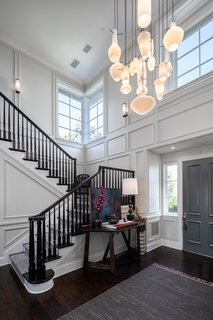 The garden walkway leads to a double-height entry hall with a contemporary chandelier composed of pendant lights of varying shapes.