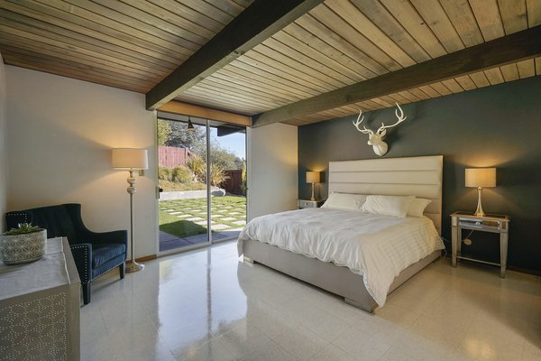 The master suite has direct access to the outdoor space via sliding glass doors. There is also an ensuite bath with updated fixtures and original cabinetry in excellent condition.