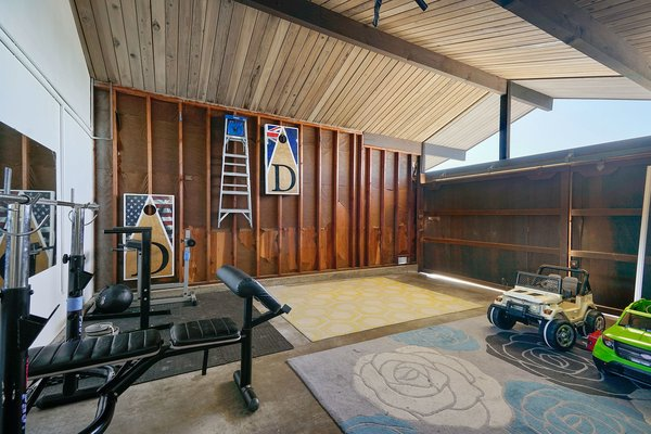 The Wood Paneled Garage Is Currently Set Up As A Home Gym And A Play