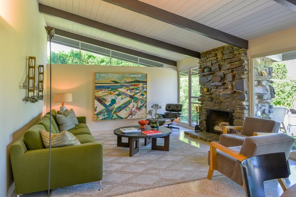 Classic midcentury features like the wall of glass and clerestory windows provide the home with a connection to the outdoors and flood the living space with natural light. A rough stone-inlay fireplace connects the living room with the facade.