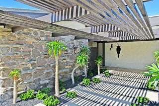 A wooden pergola shades the entrance to the home.