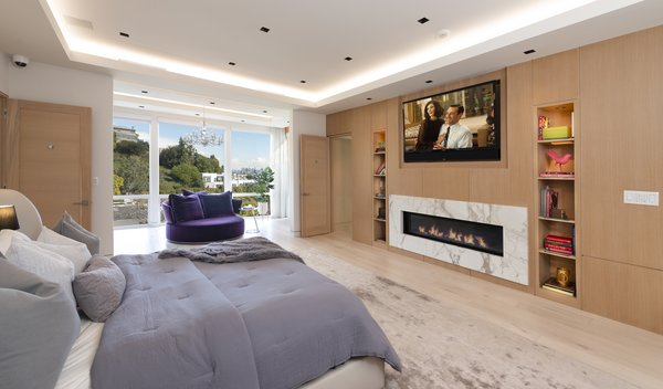 The master bedroom is equipped with two TVs, a marble-framed fireplace, a refrigerator, a microwave, and dual bathrooms—each with their own walk-in closet. Floor-to-ceiling glass doors lead to a private terrace with views of downtown Los Angeles.