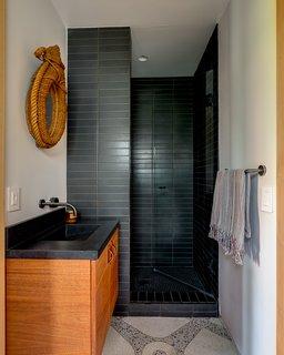 The guest bath features original brass-inlay terrazzo floors.