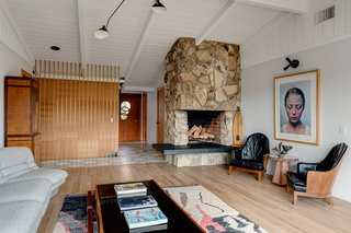 The main floor has a great room with a vaulted, tongue-and-groove ceiling and a dramatic stone-inlay fireplace.