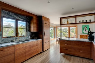 The kitchen was updated with mahogany cabinetry, including paneling on the refrigerator which matches the millwork. Marble countertops and backsplashes, paired with brass fixtures, add a luxe touch.