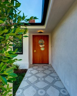 A brass-inlay terrazzo path leads to a custom-made door with a brass doorknob and a window of overlapping circles.