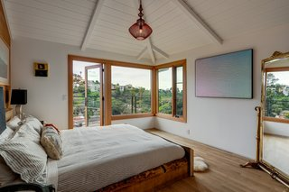 The principal suite has an open, airy feel thanks to the vaulted ceiling, picture windows,and a door leading to the outdoor terrace.