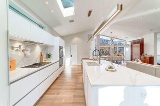 The open kitchen features a large center island, an overhead skylight, and ample storage.