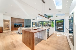 A wooden extension to the kitchen island provides additional dining space. All of the light wood flooring is new.