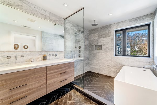 The en suite master bath features luxe marble-clad surfaces that include Carrera marble countertops and Piatra gray herringbone marble floors. There is also a deep soaking tub.