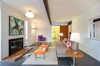 The ceilings are painted white, providing an open feel. Dark beams run the width of the home.