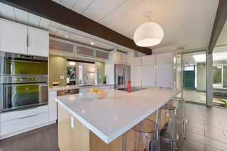 The beautifully updated kitchen has new quartz countertops, a mosaic tile backsplash, and a fast-cooking induction range. The large center island adds storage and seating.