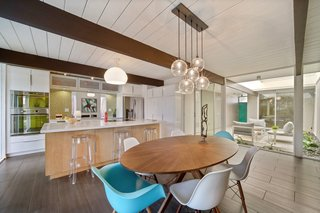The kitchen opens to the dining area, rear garden, and atrium.