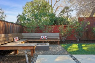 The backyard features custom built-in teak seating, a fire pit, and an organic vegetable garden.
