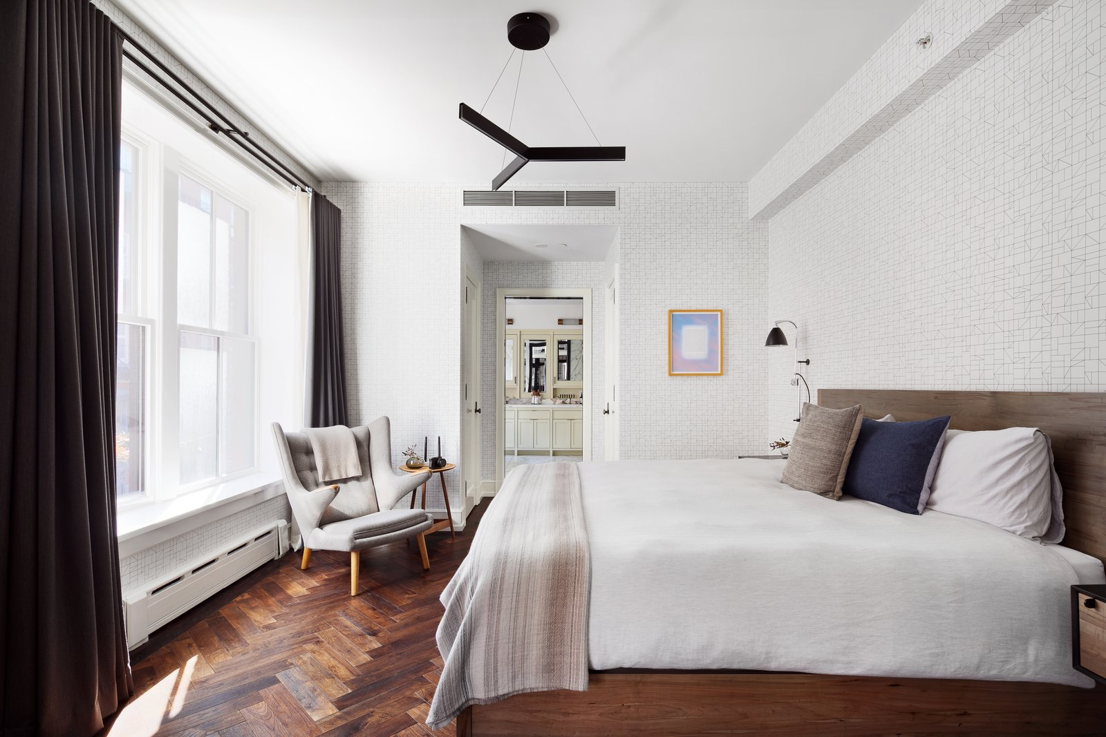 The bright and airy master suite features wallpaper from Maharam-System.  Bedroom Pendant Chair Dark Hardwood Photos from A Beautifully Bespoke Condo in Roman & Williams' Coveted Nolita Building Lists For $7M