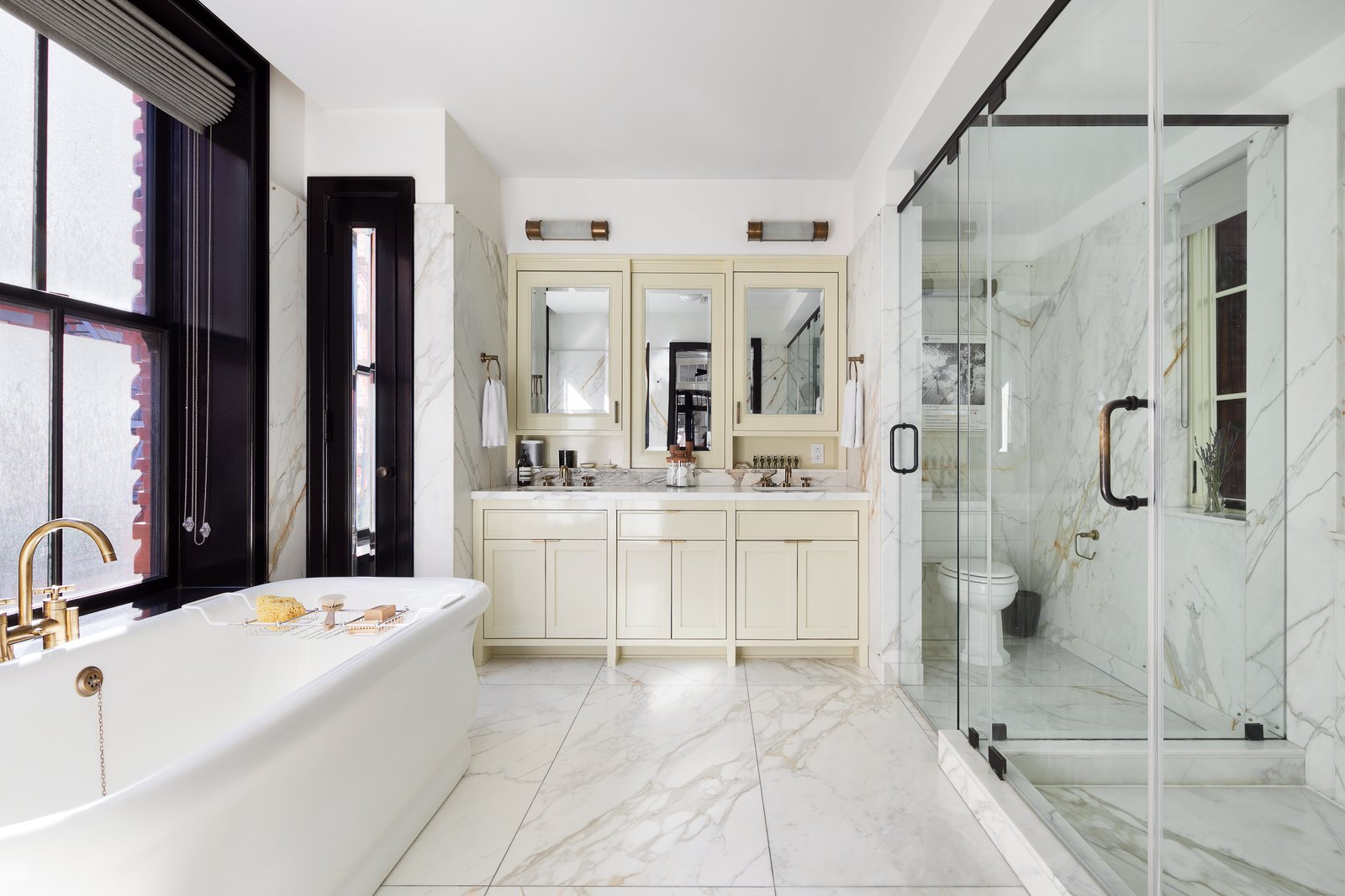 "Bath, Freestanding, Full, Marble, Enclosed, and Two Piece Roman & Williams designed the bathrooms with ""the look and feel of a grand European hotel"". The double vanity is painted a high-glass cream and slabs of Calacatta marble is mixed with brass fixtures makes the master bath shine.  Bath Two Piece Freestanding Full Photos from A Beautifully Bespoke Condo in Roman & Williams' Coveted Nolita Building Lists For $7M"