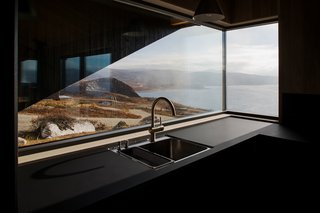 The butted-glass corner window brings panoramic views into the kitchen.