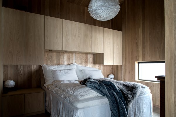 At the back of the cabin, there is a master bedroom, a bathroom, and a sauna that ingeniously doubles as a guest room.