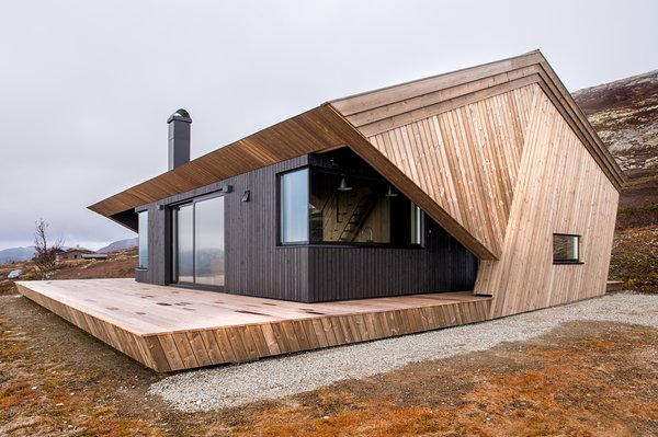 The angled pine paneling set against the black cabin body creates a strong geometric form.