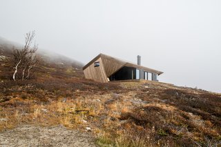 "Located on the Imingfjell mountainside in Norway, this minimalist, 785-square-foot cabin features a ""hood"" in response to the climate and the region's strict building regulations."