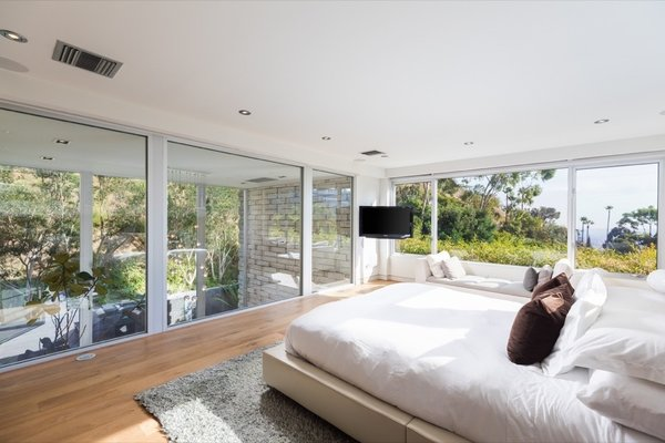 The bright and airy master bedroom has windows overlooking the living room below.