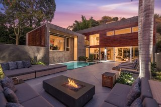 The backyard has a zero-edge swimming pool and a spacious lounge area with a fire pit. There's also a high privacy wall topped by a perfectly manicured privacy hedge.