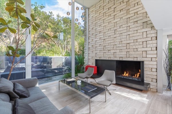 The living space features walls of glass that overlook a serene garden patio and full-height glass sliding doors open the living room to the front yard for true indoor/outdoor living.