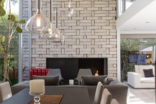 The double-height space is anchored by a brick fireplace with a midcentury vibe.