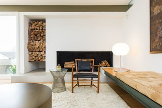 The living room in this California home has a wood-burning fireplace and a dedicated nook for firewood storage. The nook is tall and narrow while the fireplace opening itself is long and short, creating an exciting and engaging composition on the wall.