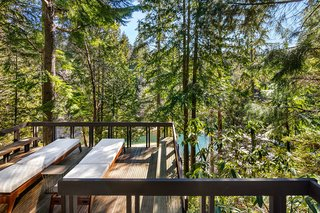 The deck looks out over the forest, with a glimpse of the lake.