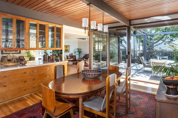 Sliding glass doors connect the dining area to a long deck that lines the exterior.