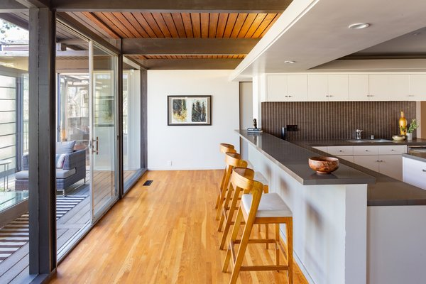 Solid beams support the tongue-and-groove wood-paneled ceiling, which extends to the exterior of the home. Every room is connected to the outdoors.