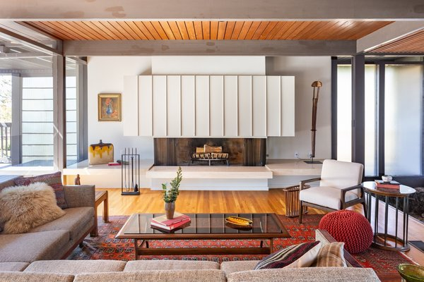The open living room is anchored by a large fireplace and connected to the dining room and kitchen.