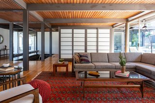 The open plan is visually broken up by the use of shoji screens and beams.