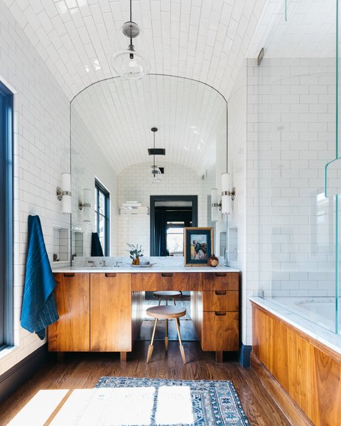 The master bathroom features a coved tile ceiling, a custom walnut vanity, and a large soaking tub.