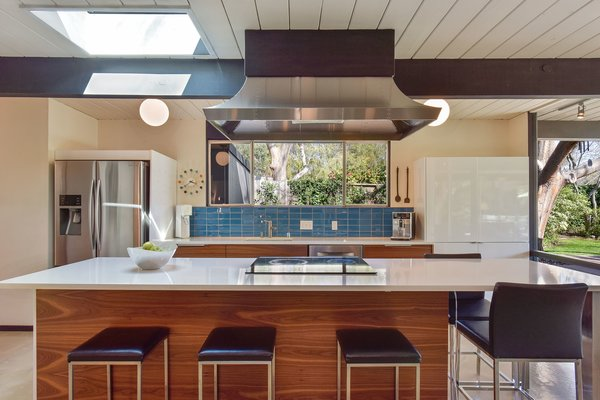 The updated kitchen of this circa-1969 Claude Oakland-designed Eichler has walnut-paneled cabinetry, quartz countertops, a turquoise tile backsplash, and a large center island with seating.