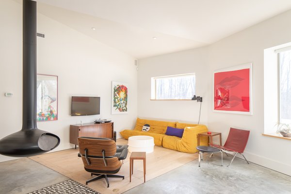 A hanging orb fireplace and an insert of warm wood flooring help define the living room within the open floor plan.