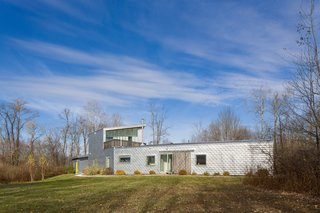 The modern home is surrounded by acres of woodland.