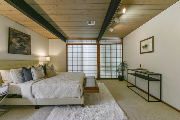 The master bedroom has a Japanese vibe thanks to shoji screens, which slide to reveal