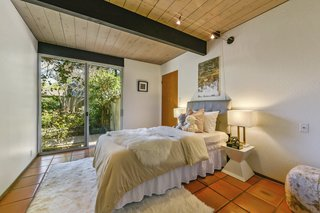 The fifth bedroom features sliding glass doors that lead to the garden.