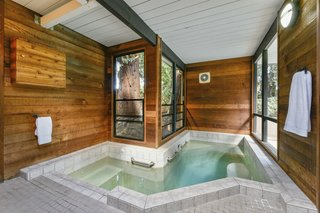 Tucked behind the shoji screens is a spectacular spa with cedar-paneled walls, large glass windows, and a sliding glass door leading to the backyard.