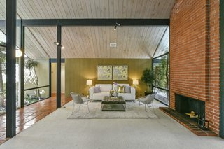 The great room has soaring ceilings and elegant midcentury lines.