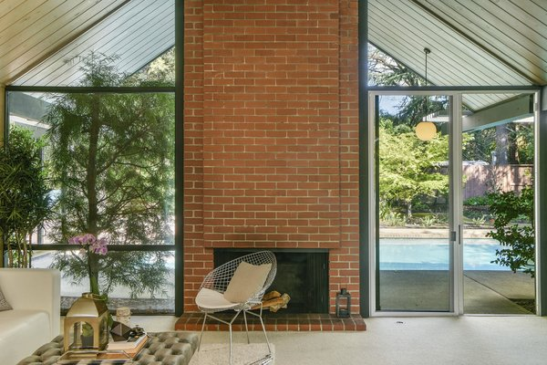 A bold wood-burning brick fireplace framed by glass anchors the open-plan living space.