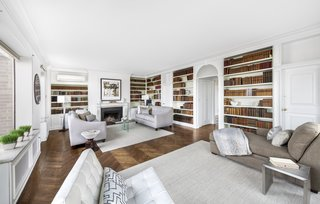 The 28-foot corner living room features built-in bookshelves, a wood-burning fireplace, and the original herringbone floor. Five windows provide sweeping views of the surroundings.