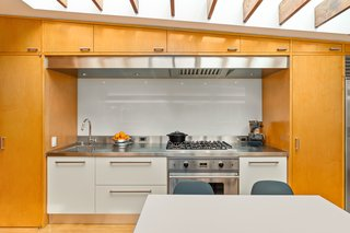 The updated, contemporary kitchen maintains a warm midcentury presence thanks to the use of wood.