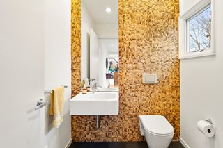 This updated bathroom features a fully tiled wall.