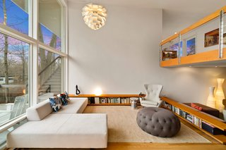 The double-height living room is open and airy thanks to an expansive wall of windows.